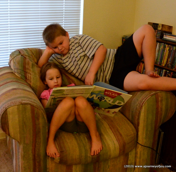 Samuel and Claire reading the Children's Atlas of God's World.